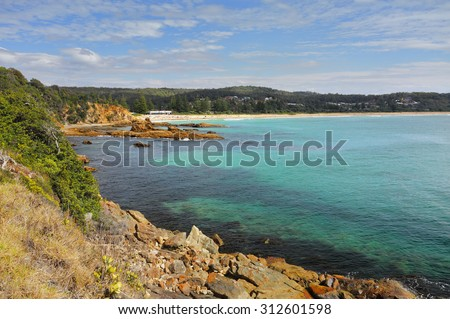 Tathra is a seaside village on the far south coast, called the Sapphire Coast in the Bega Valley shire.  Views from the rocky headland looking back towards Tathra beach.on a beautiful sunny day - stock photo