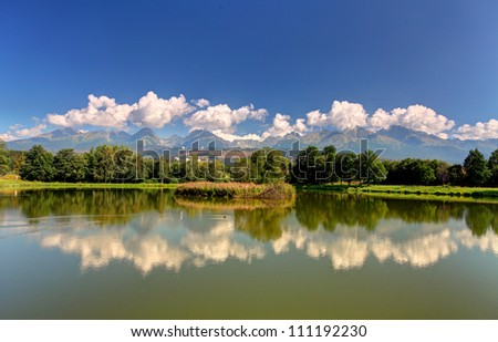 Tatra mountain with reflection in lake - panoramic view - stock photo