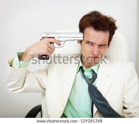 Tattered business man in white suit keeps gun near his temple on black background - stock photo