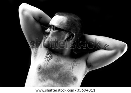 Tattoed biker shows you his muscle - stock photo