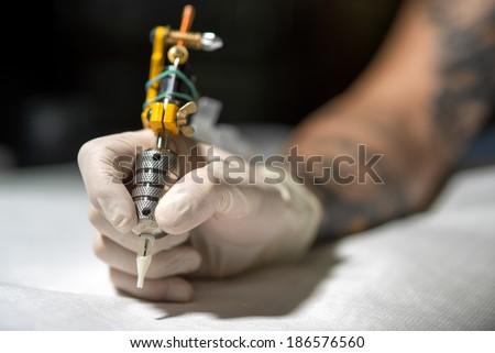 Tattoo artist at work. Closeup - stock photo