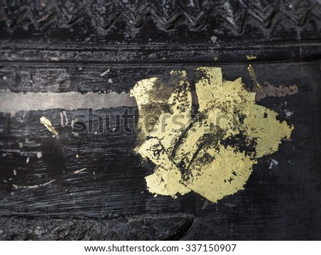 Tattoo by gold color onto solid iron surface of bell