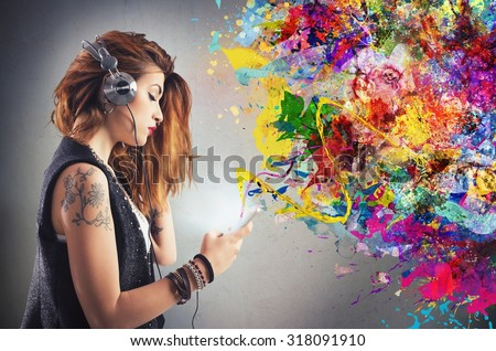 Tattoo girl listens to music with headphones - stock photo