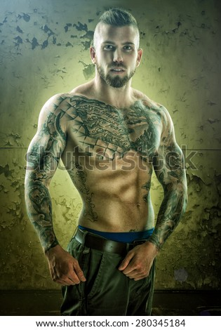 Tattoo, unique muscle-building man, standing in front of the wall - stock photo