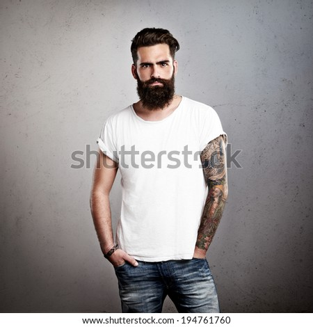 Tattooed brutal man wearing white t-shirt - stock photo