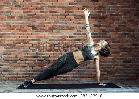 tattooed female doing exercises indoors, sporty woman practicing yoga - stock photo