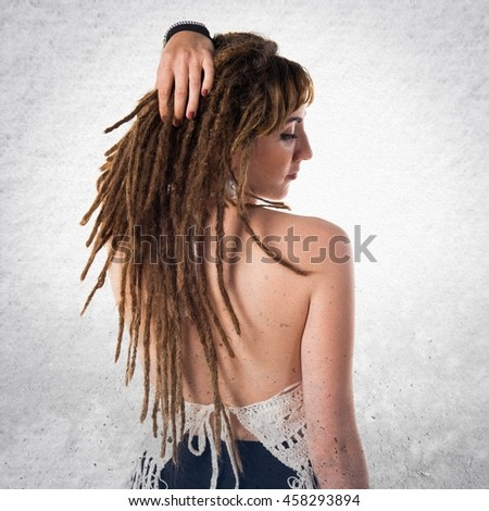 Tattooed girl with dreadlocks over textured background