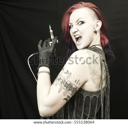 Tattooed girl with red and violet hair in different poses with tattoo machine as tattoo master. Master works. Black background and sterile black gloves. Emotional face. Tattoo glasses.