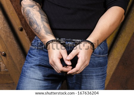 Tattooed hands of a criminal handcuffed. Rear view. - stock photo