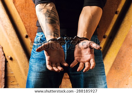 Tattooed hands of a criminal handcuffed. Rear view.