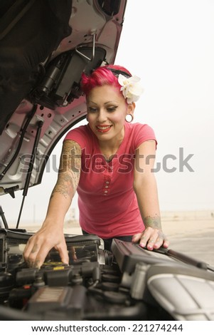Tattooed Hispanic woman looking under car hood