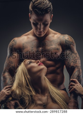 Tattooed male and female. Isolated on grey background. - stock photo