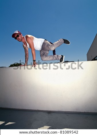 tattooed male parkour free runner climbing over a wall