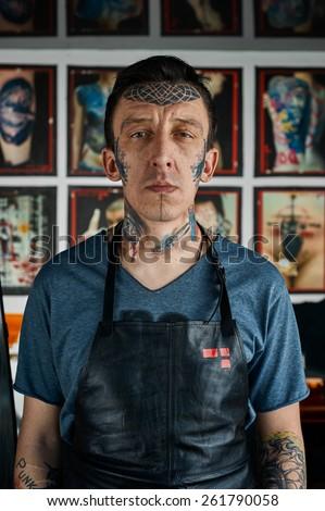 Tattooed man in black leather apron - stock photo
