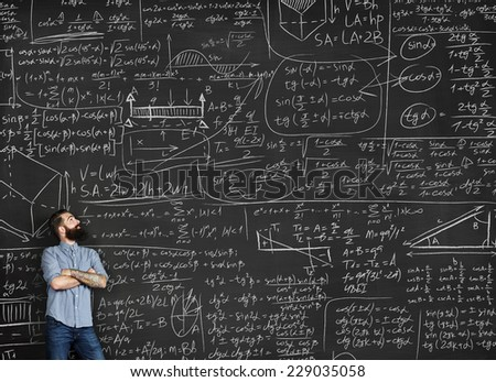 Tattooed man looking at chalkboard with formulas - stock photo