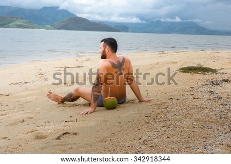Tattooed man relaxing on the beach in tropical country. - stock photo