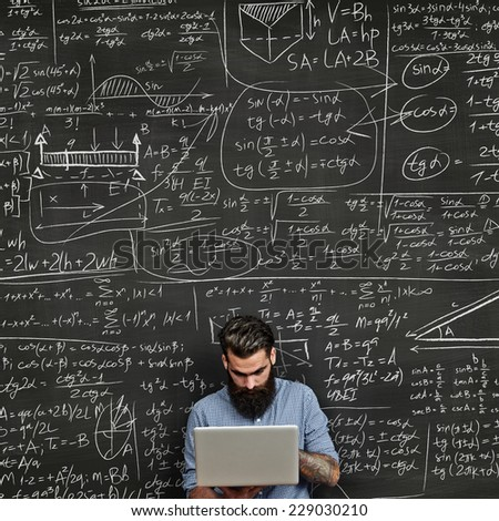 Tattooed man working with laptop near chalkboard with formulas - stock photo