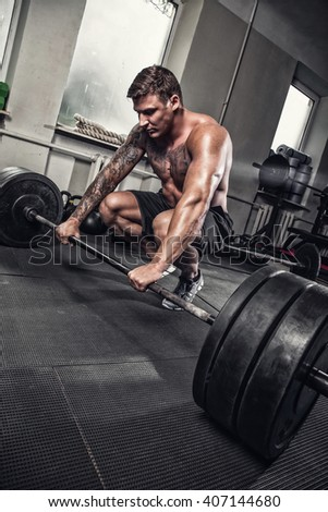 Tattooed muscular man standing on knees with barbell in a gym club. - stock photo