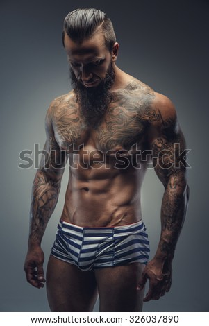Tattooed muscular man with beard in stripes panties. Isolated on grey background. - stock photo