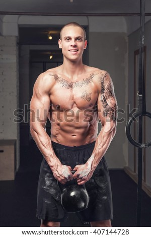 Tattooed shirtless man holds lifting weight in a gym club.