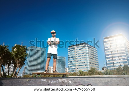 Tattooed skater in plain blank t-shirt stands on his londoard on top of concrete pool in skatepark in front of urban landscape