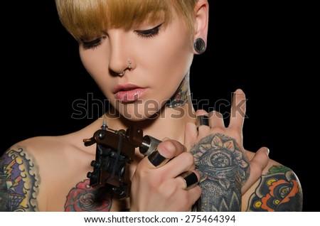 tattooed young woman with tattoo machine, dark background - stock photo