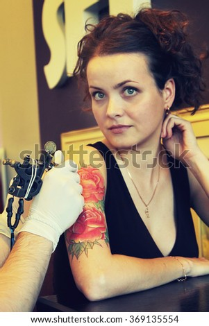 tattooer showing process of making a tattoo on young beautiful hipster woman with red curly hair. Tattoo design in the form of rose. Vintage picture - stock photo