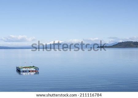 TAUPO, NEW ZEALAND - JULY 24: Lake Taupo, hole in one floating platform on calm lake and view across lake to snowcapped mountains on July 24, 2014. Taupo and the lake is a center for adventure tourism - stock photo