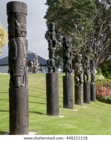 Tauranga, New Zealand - May 26, 2016: Maori carving style wood figures at Gate Pa with Puhirake statue on a foreground.