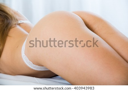 Taut bottom of female in bed with white linen