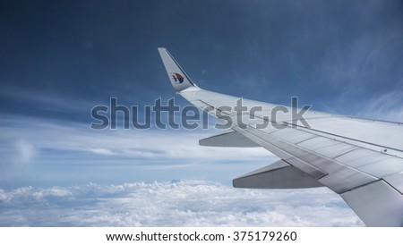 Tawau, MALAYSIA - May 9, 2015 : Soft focus of Malaysian Airline System (MAS) aeroplane wing over cloud and blue sky.
