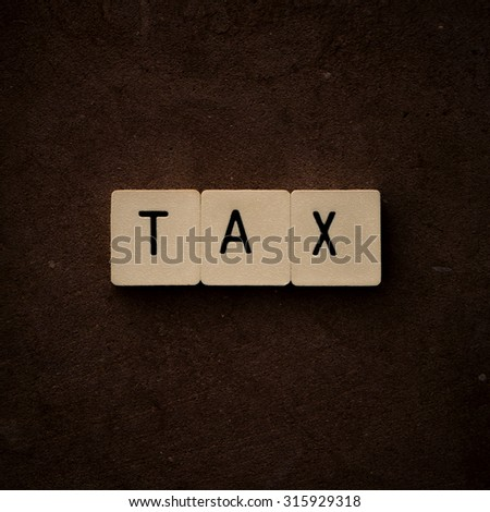 TAX. A stylized photo of the word 'tax' on terracotta with 'craquelure' effect.