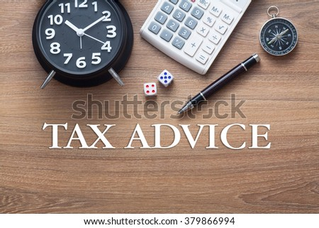 Tax Advice words written on wooden table with clock,dice,calculator pen and compass - stock photo
