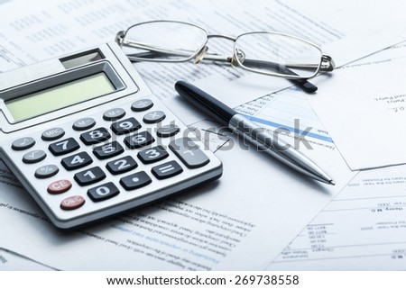 Tax. Calculating numbers for income tax return with pen and calculato - stock photo