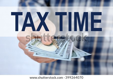 Tax Concept. Man holding dollars in hand - stock photo