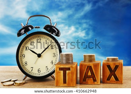 Tax concept. Tax time and alarm clock with coins on table - stock photo