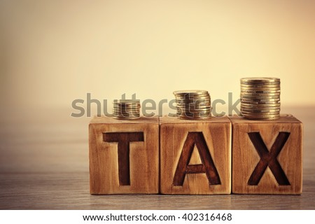 Tax concept with wooden blocks and coins on table - stock photo