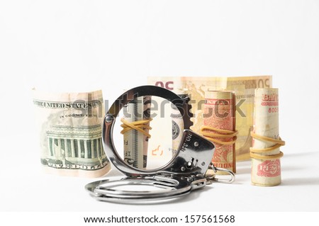 Tax Crime Concept Money and Handcuffs on a White Background - stock photo