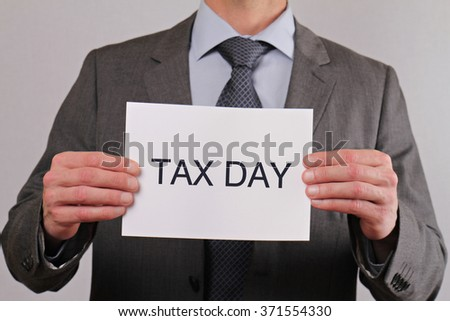 Tax day. Close up of businessman showing card.  Business, teamwork and finance concept. - stock photo