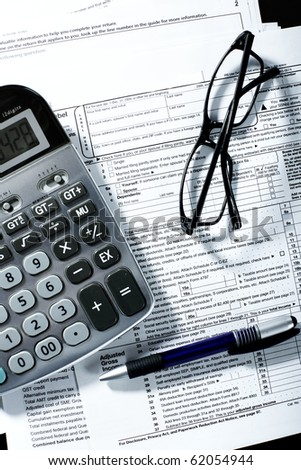 Tax form, a calculator, a pen on the table - stock photo