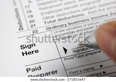 Tax form and hand writing with a pen