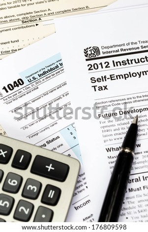 Tax form and instruction with pen, and calculator taxation concept