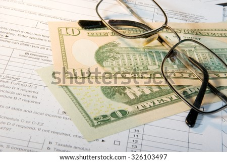 Tax form business financial concept - individual return tax form with money and glasses