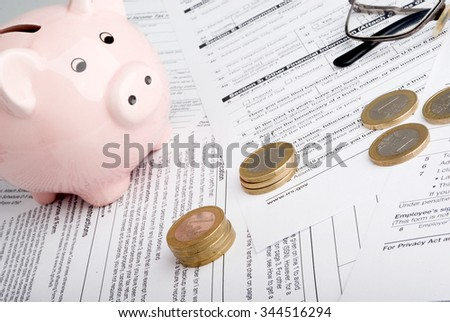 Tax form business financial concept - individual return tax form with money, glasses and piggy bank - stock photo