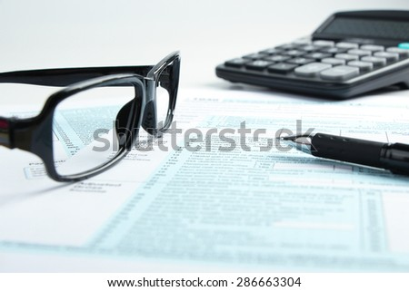 Tax form business financial concept with a pen, a pair of glasses and a calculator aside. - stock photo