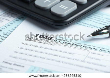 Tax form business financial concept with a pen and a calculator aside. - stock photo