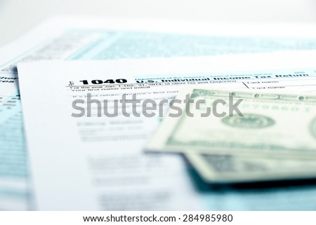 Tax form financial concept with money and some other business objects aside. - stock photo