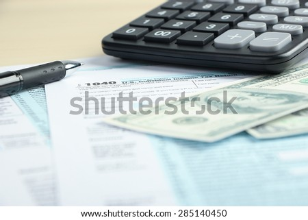 Tax form financial concept with some money and some other business objects aside.