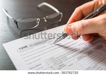 Tax form 1040 for individual tax return with pen and glasses - stock photo