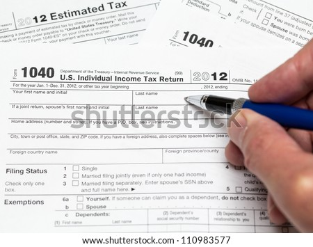 Tax form 1040 for tax year 2012 for US individual tax return with hand